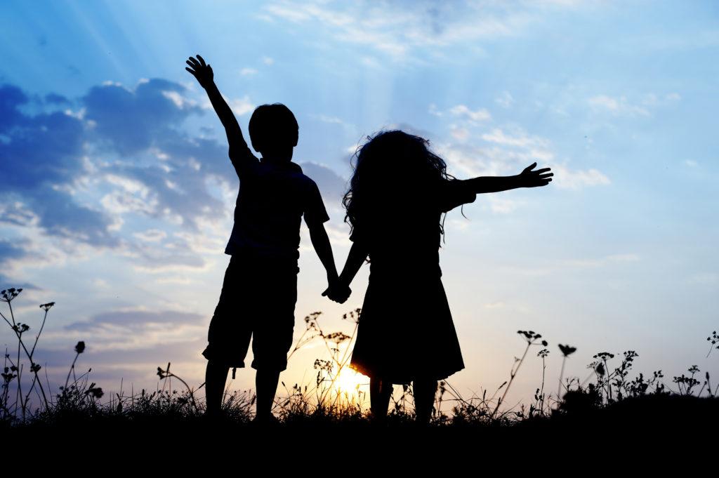 תמונת ילדים אוחזים ידיים בשקיעה