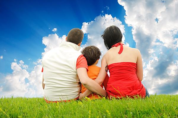 תמונה של משפחה יושבת על הדשא